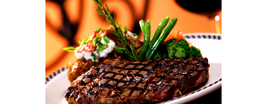 bad website steak house, picture of a delicious looking steak next to asparagus and vegetables