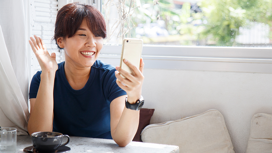 Young female talking with her friend on smartphone device